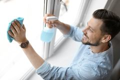 Man washing window glass at home. Man in casual clothes washing window glass at home Royalty Free Stock Image