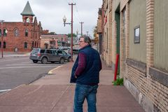 Man in casual clothing walking down sidewalk in small town royalty free stock photography