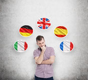 Man in casual shirt holds his chin and thinks about which language to study. Italian, German, United Kingdom, Spanish and Fr. Young man in casual shirt holds his Royalty Free Stock Photo