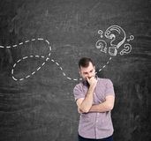 A man in casual shirt is thinking about unanswered questions. Question marks are drawn on the black chalkboard. A young man in casual shirt is thinking about Royalty Free Stock Image