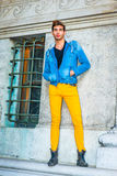 Man Casual Street Fashion. Man Casual Fashion. Dressing in a blue jacket with hood, black underwear, yellow pants, leather boot shoes, hands in pockets, a young Stock Photos