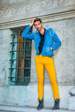 Man Casual Street Fashion. Man Casual Fashion. Dressing in a blue jacket with hood, black underwear, yellow pants, leather boot shoes, a young handsome guy is Royalty Free Stock Images