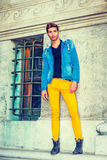 Man Casual Street Fashion. Man Casual Fashion. Dressing in a blue jacket with hood, black underwear, yellow pants, leather boot shoes, a young handsome guy is Stock Photos