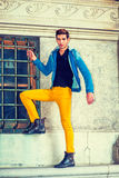 Man Casual Street Fashion. Man Casual Fashion. Dressing in a blue jacket with hood, black underwear, yellow pants, leather boot shoes, a young handsome guy is Stock Image