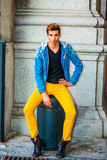 Man Casual Street Fashion in New York. Man Casual Fashion. Dressing in a blue jacket with hood, black underwear, yellow pants, leather boot shoes, a young Royalty Free Stock Photo