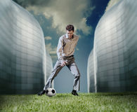 Man in casual suit playing in football near the modern building Royalty Free Stock Photos