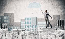 Study hard to become successful businessman. Man in casual wear keeping hand with book up while standing among flying letters with drawn cityscape on background Stock Image
