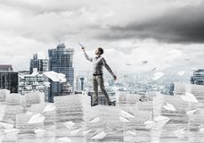 Study hard to become successful businessman. Man in casual wear keeping hand with book up while standing among flying paper planes with cityscape on background Royalty Free Stock Photos