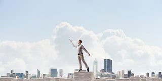 Study hard to become successful businessman. Man in casual wear keeping hand with book up while standing on pile of documents with cityscape on background Stock Photo