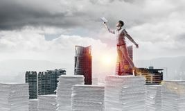 Study hard to become successful businessman. Man in casual wear keeping hand with book up while standing on pile of documents with cityscape and sunlight on Royalty Free Stock Photography