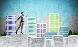 Study hard to become successful businessman. Man in casual wear keeping hand with book up while standing on pile of paper documents with drawn cityscape on Stock Photos