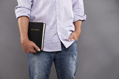 Man Casually Holds Bible. A man stands indoors with one hand holding a black bible and the other hand casually in his jeans pocket Stock Images