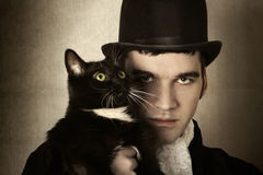 Man and cat. Stylized retro portrait of man in top hat and period clothing with black cat stock photos