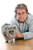 Man and cat. Middle aged man laying on floor next to Silver furred cat Stock Photography