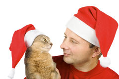 Man and cat in Santa's hat looking at each other Royalty Free Stock Images