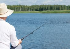 A man catches fish on the background of blue water, rear view stock images