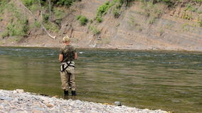 Man catches fish in the river. man fishing with a rod and reel. stock footage