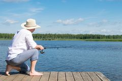 Man catches fish from the shore of a beautiful lake in the forest stock image