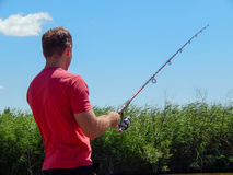 A man catches a fish on a spinning. Fishing in the summer Stock Photo