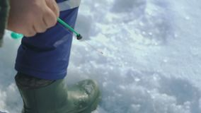 Man catches fish on winter lake stock video