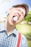 Man catches golf ball in mouth Royalty Free Stock Photography
