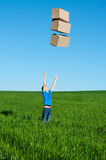 Man catching boxes on green field Stock Photo