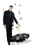 Man catching dollars by umbrella Stock Photos