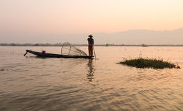 A man catching fish at sunrise on the lake in Inlay, Myanmar Royalty Free Stock Photos