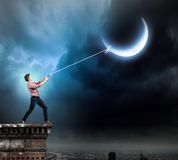 Man catching moon Stock Photo