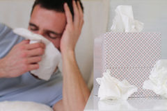 Man caught cold , flue, running nose, selective  focus on  tissue box Royalty Free Stock Photo