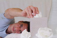 Man caught cold , flue, running nose, selective  focus on  tissue box Royalty Free Stock Photos