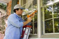 Man Caulking Window. Man on ladder caulking outside window