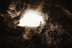 Man at cave entrance with giant cliffs Royalty Free Stock Photo