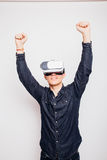 Man celebrate victory experiencing virtual reality through a VR headset isolated on white background. Young man celebrate victory experiencing virtual reality Royalty Free Stock Photography