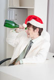 Man celebrates Christmases at office on workplace Royalty Free Stock Image