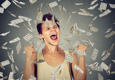 Man celebrates success under money rain falling down dollar bills. Happy young man going crazy screaming super excited. Ecstatic guy celebrates success under Stock Images