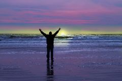 Man celebrates sunrise on a beach. Concept of a man joyously greeting early dawn on a beach stock photography