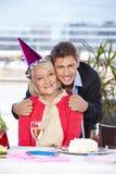 Man celebrating birthday with his. Happy adult men celebrating birthday with his senior mother Royalty Free Stock Photos