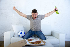 Man celebrating goal at home couch watching football game on television Stock Photography