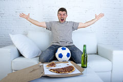 Man celebrating goal at home couch watching football game on television Stock Photos
