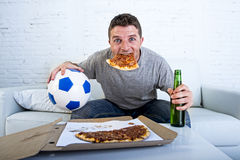 Man celebrating goal at home couch watching football game on television Stock Photo