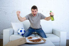 Man celebrating goal at home couch watching football game on television Stock Images