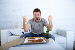Man celebrating goal at home couch watching football game on television Stock Image