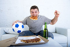 Man celebrating goal at home couch watching football game on television Royalty Free Stock Image