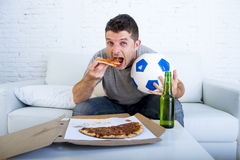 Man celebrating goal at home couch watching football game on television Royalty Free Stock Photos