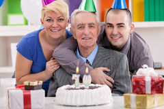 Man celebrating his 70th birthday. Senior men celebrating his birthday with family, ready to blow out the many candles on his cake Royalty Free Stock Images