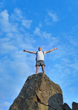 Man celebrating reaching the top of a mountain Royalty Free Stock Images