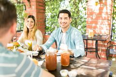 Man Celebrating Reunion With Friends At Restaurant. Handsome men having fun while partying with friends at outdoor restaurant royalty free stock photo