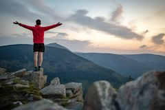 Man celebrating sunset looking at view in mountains royalty free stock photo