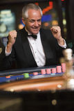 Man celebrating win at roulette table. In casino Royalty Free Stock Photo